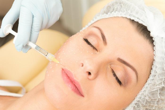 Esteticista aplicando inyección de colageno